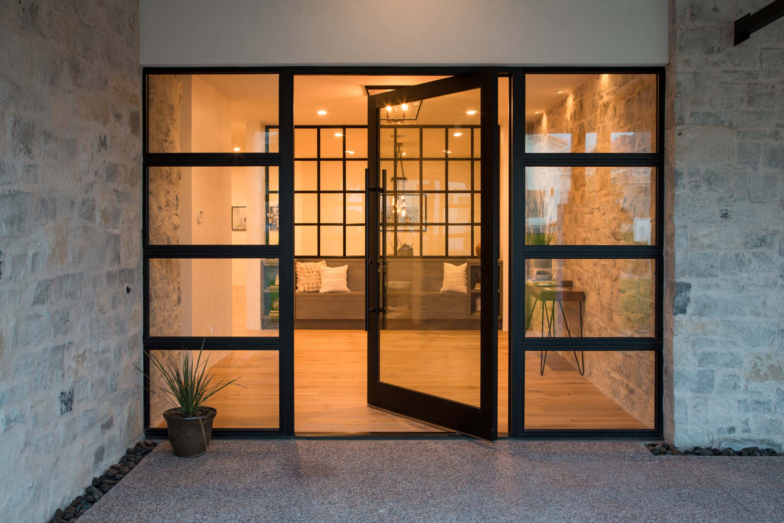 A massive pivot door greets visitors to the dramatic front entry.