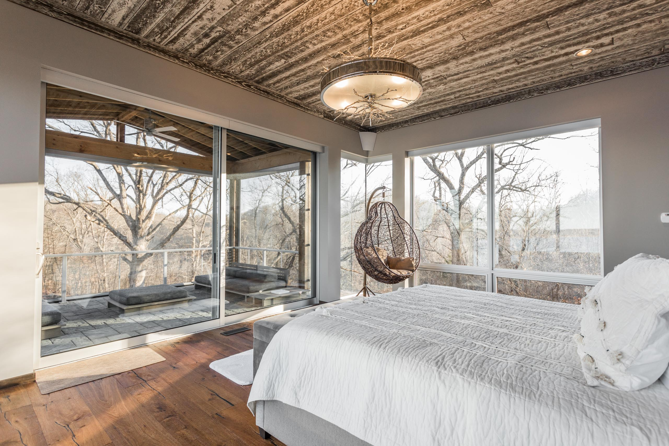 Huge panels of glass bring the outdoors in to this cozy bedroom.