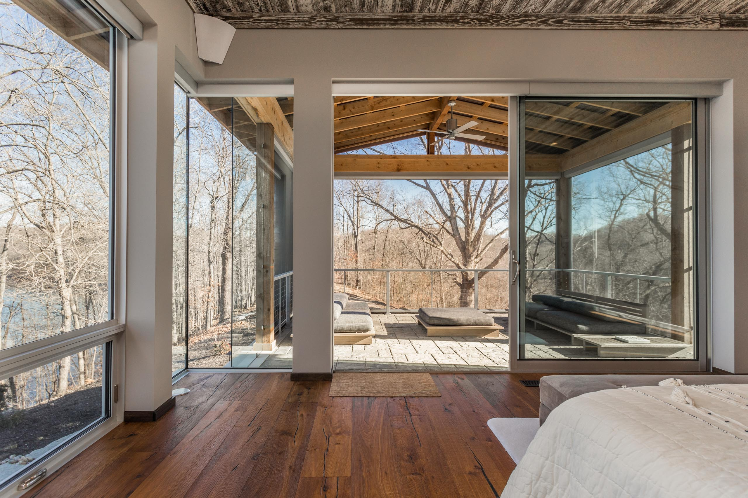 A huge sliding glass door opens from the master bedroom to an enclosed outdoor living space.