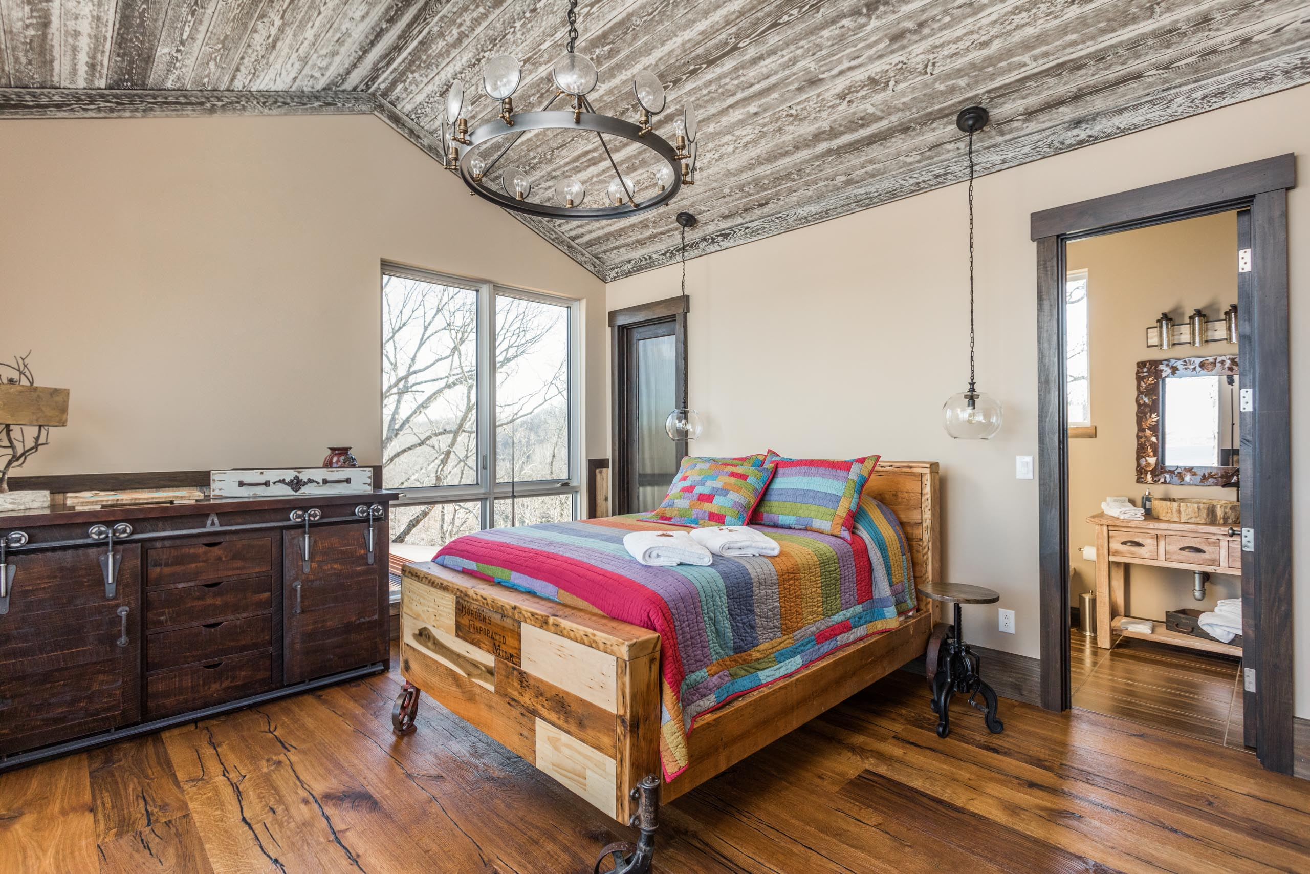 This rustic guest bedroom is bathed in natural light thanks to a pair of casement windows from Western Window Systems.