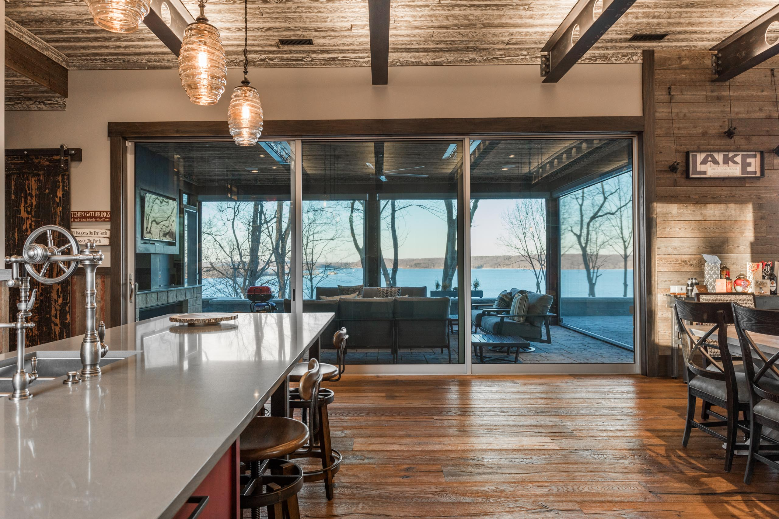 A massive multi-slide door opens from the kitchen/living area to a giant outdoor living space overlooking the lake.