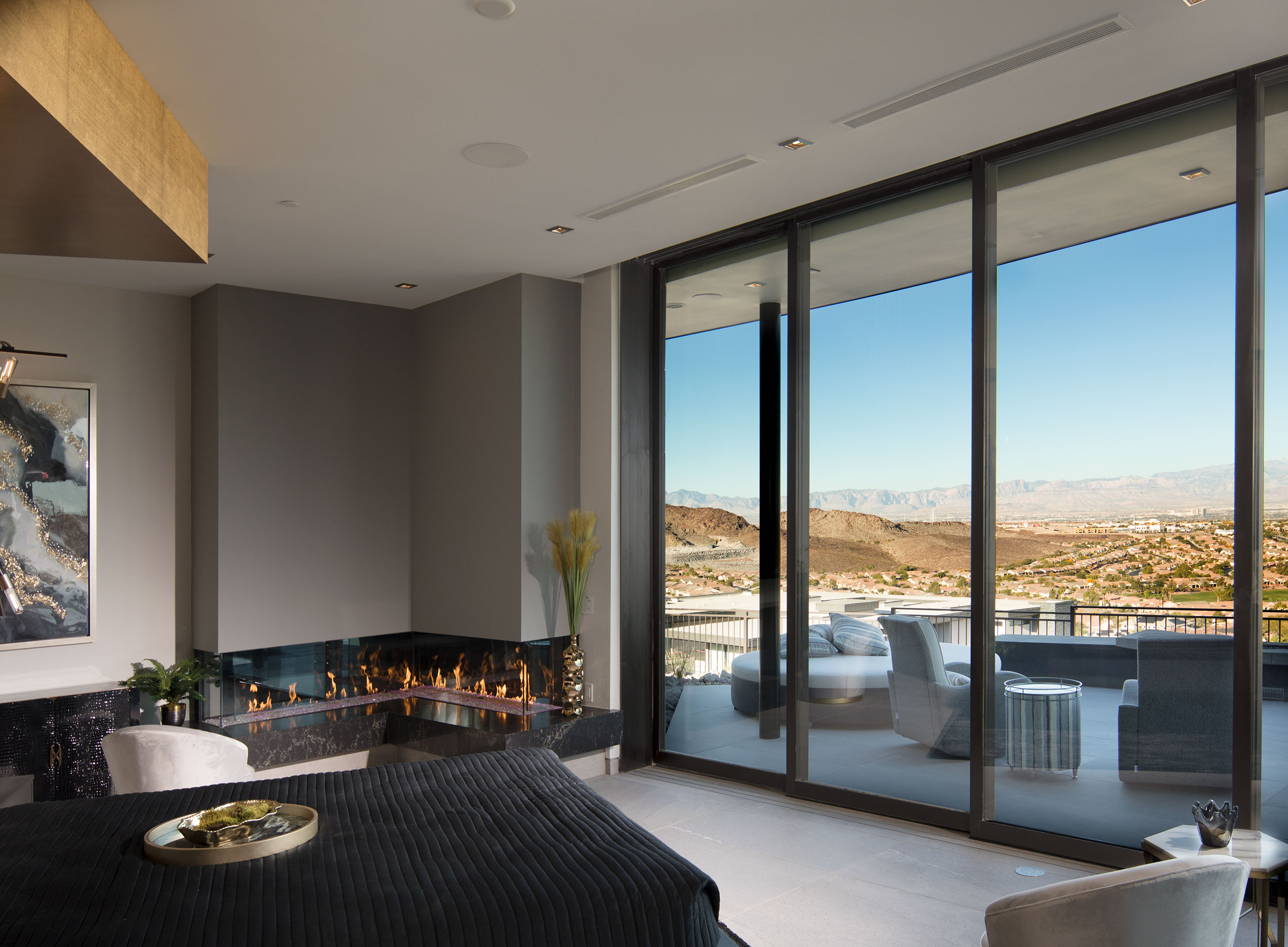 The master suite features large sliding glass doors that open onto a private patio with views of the Las Vegas Valley.