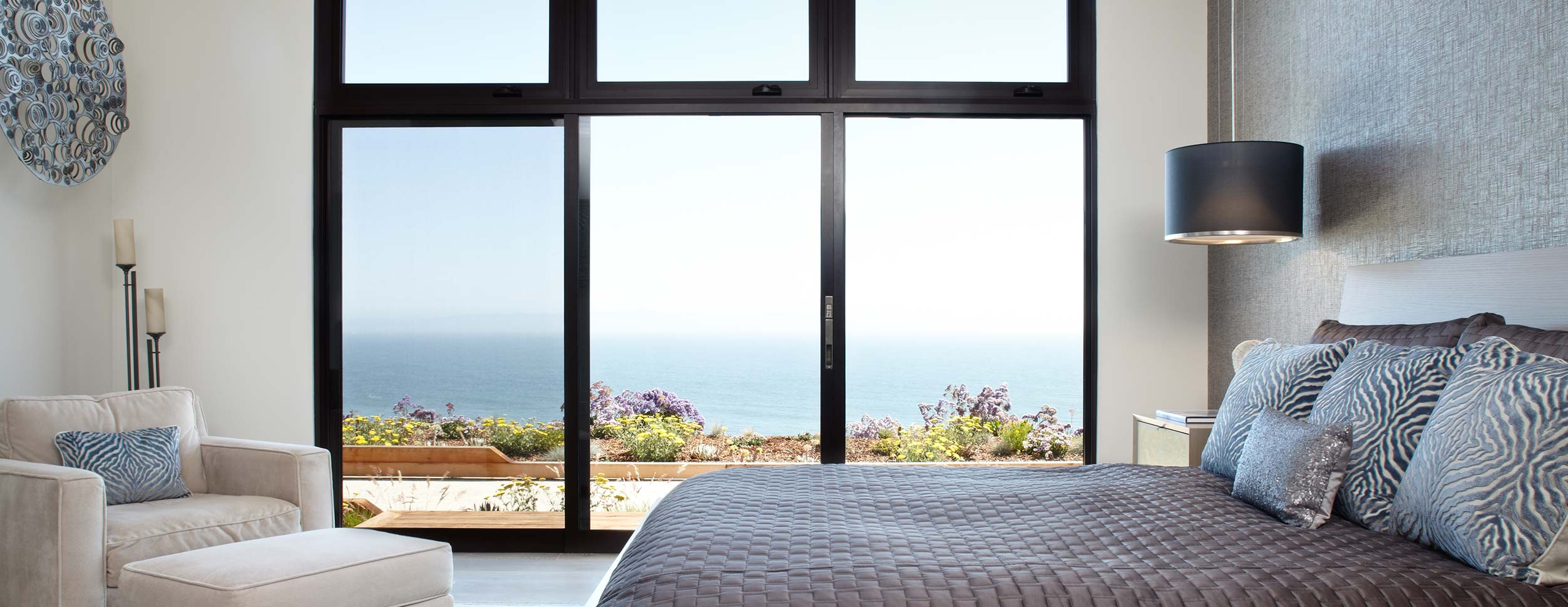 The master bedroom features a giant sliding glass door that opens up to the Pacific Ocean.