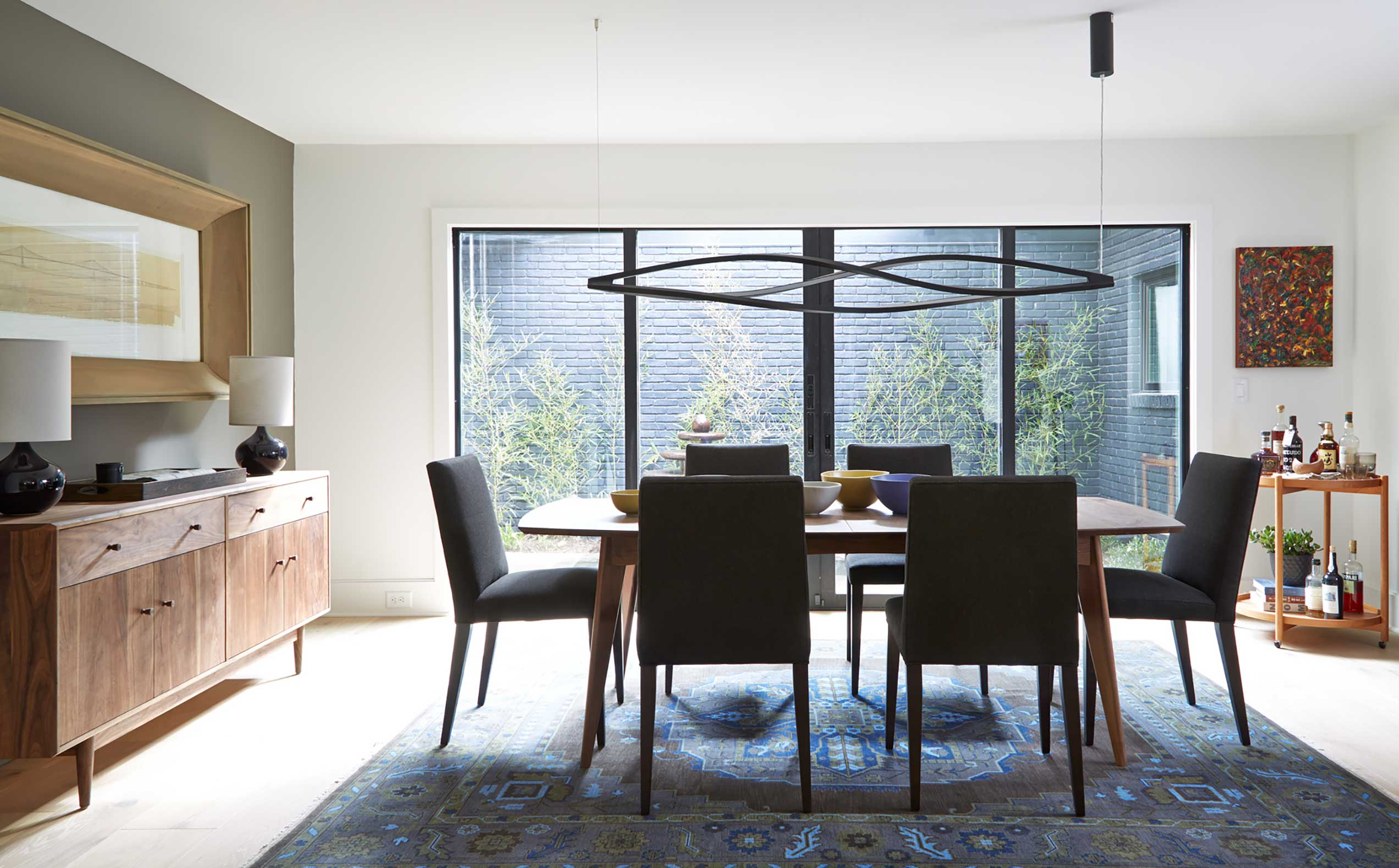 The dining room features a pair of sliding glass doors whose contemporary appeal fits the home's updated Midcentury Modern styling.