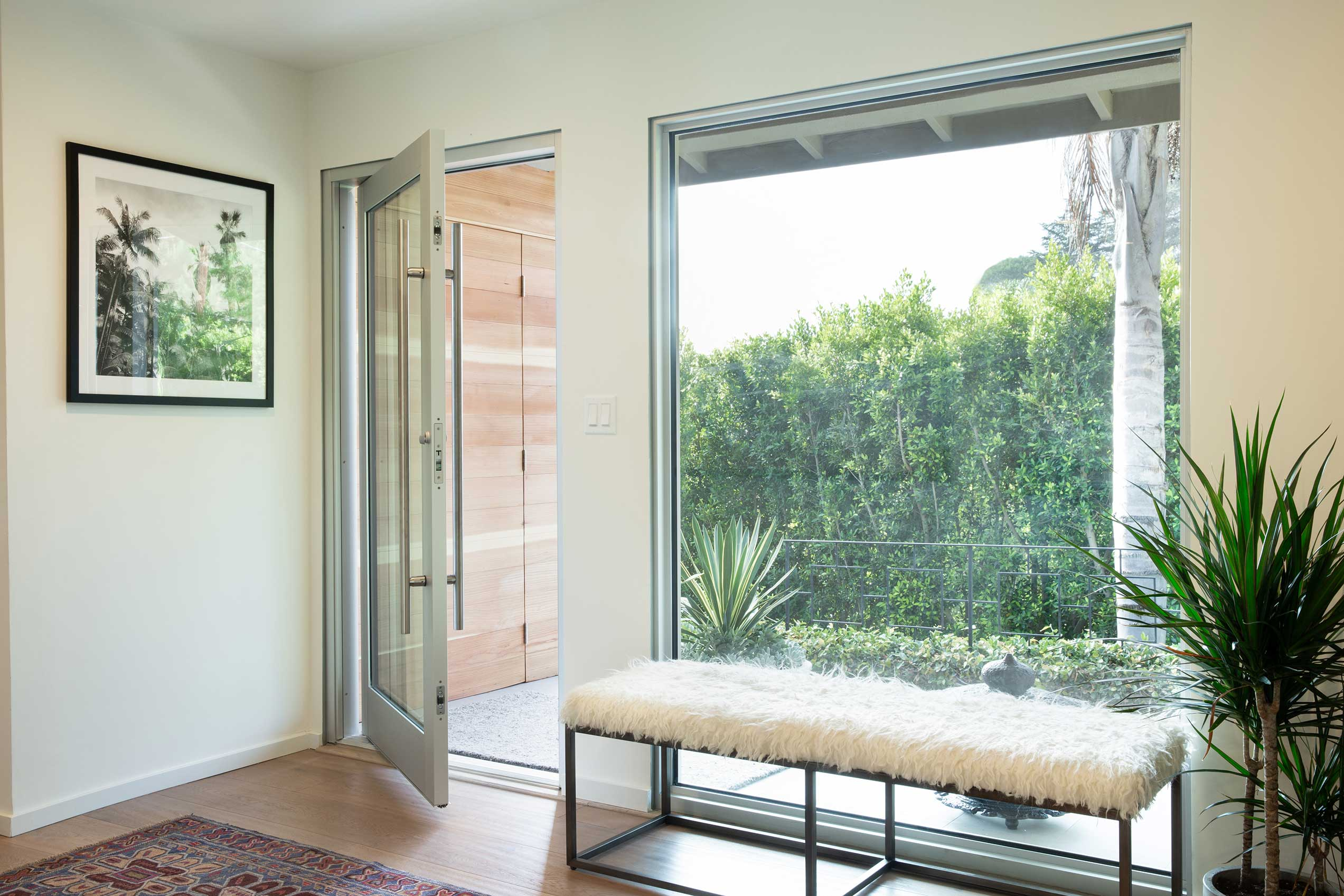 A pivot door and large fixed window provide energy efficiency to go along with clean, contemporary aesthetics.