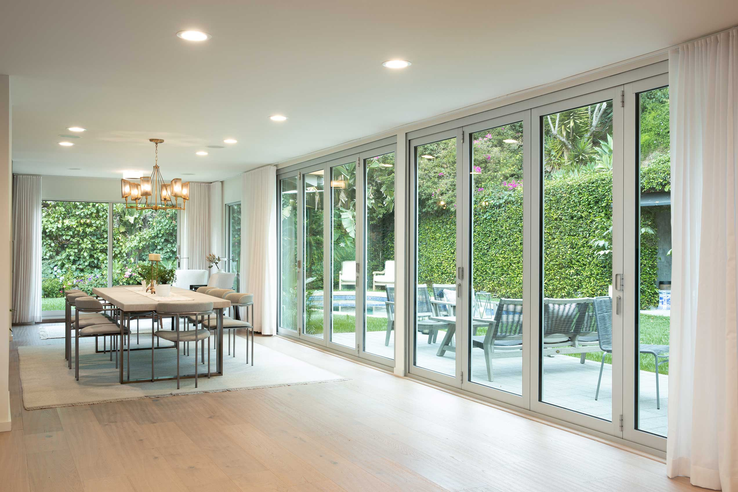 Two giant bi-fold doors completely open up the living/dining spaces to the pool and outdoor patio.