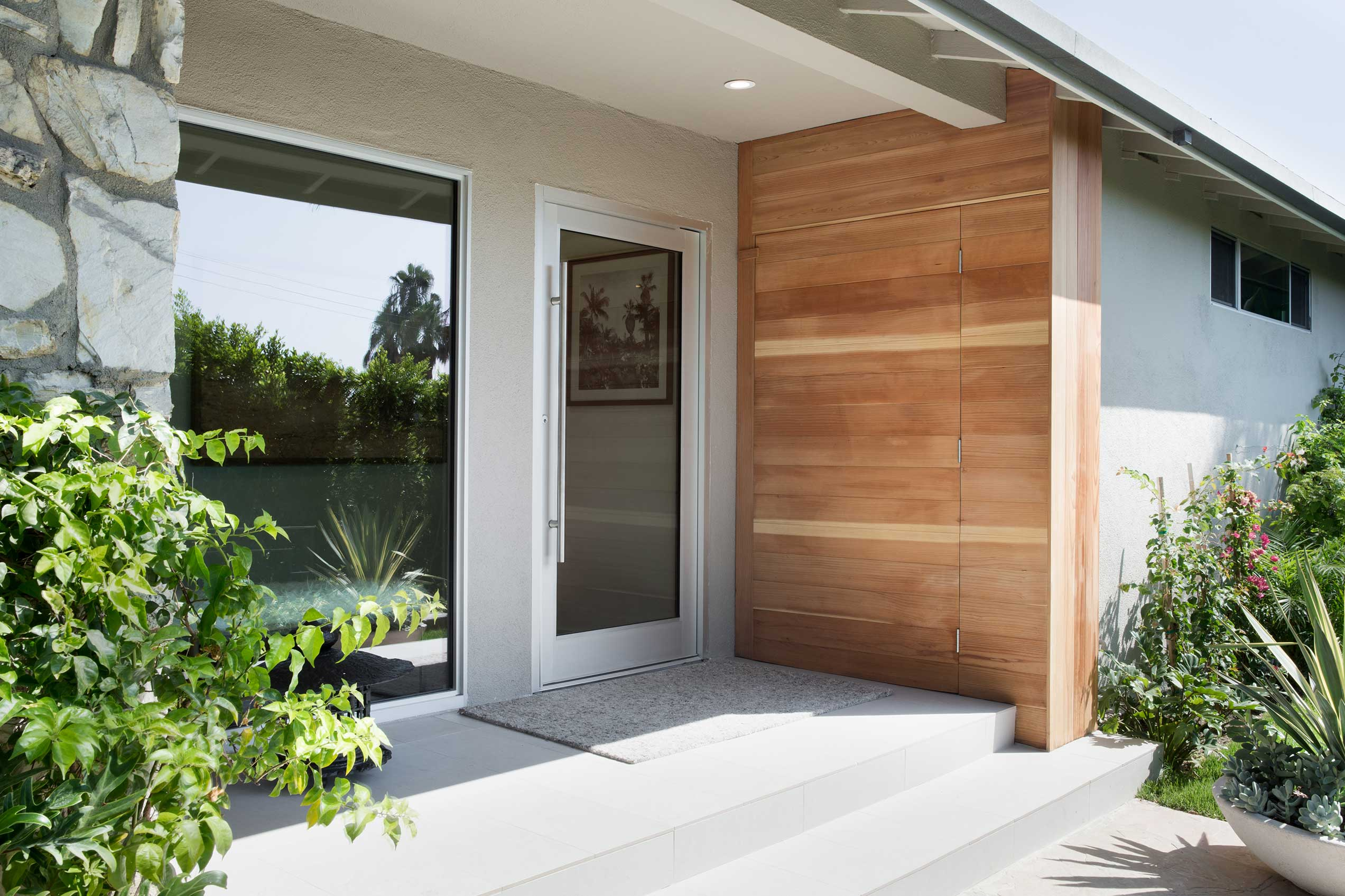 The front of the house is as beautiful as the back, with this pivot door and large fixed window.