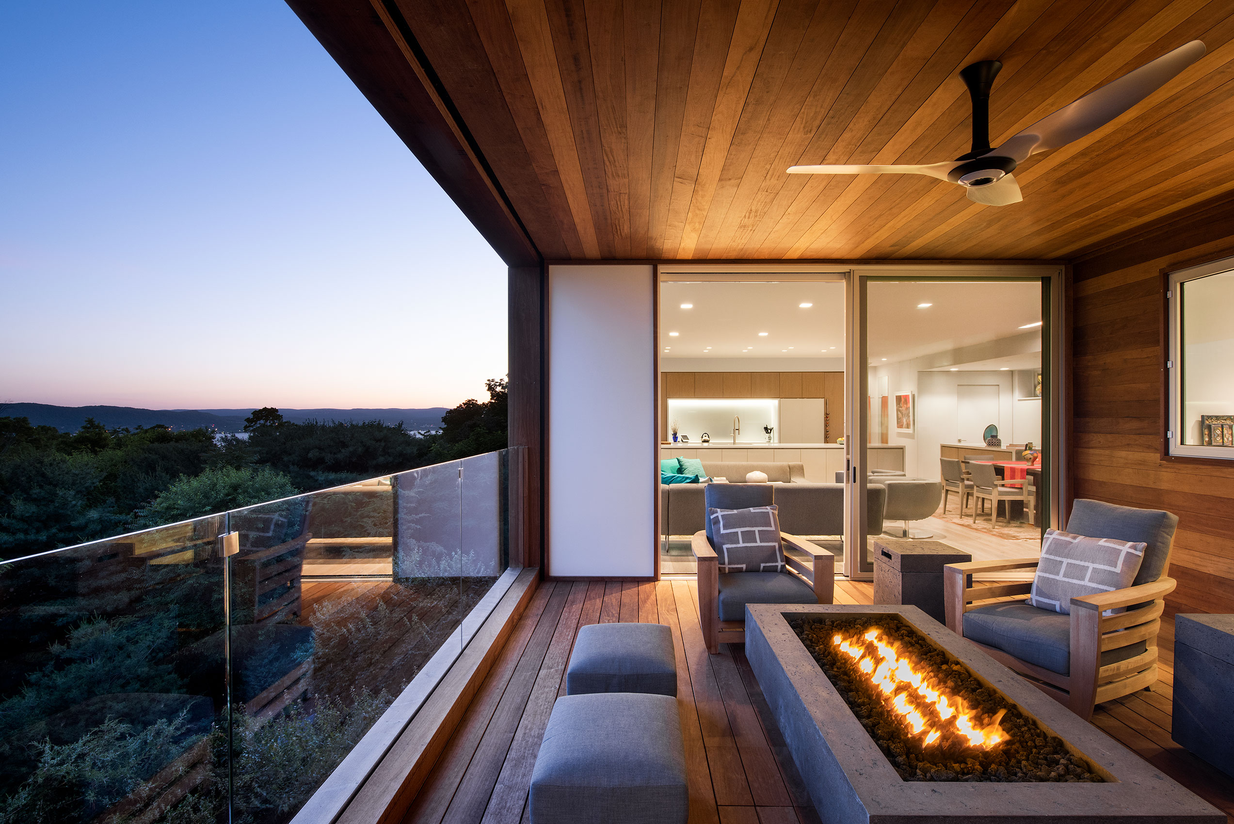 Glass fencing preserves the uninterrupted views while a concrete fire table keeps the deck cozy.