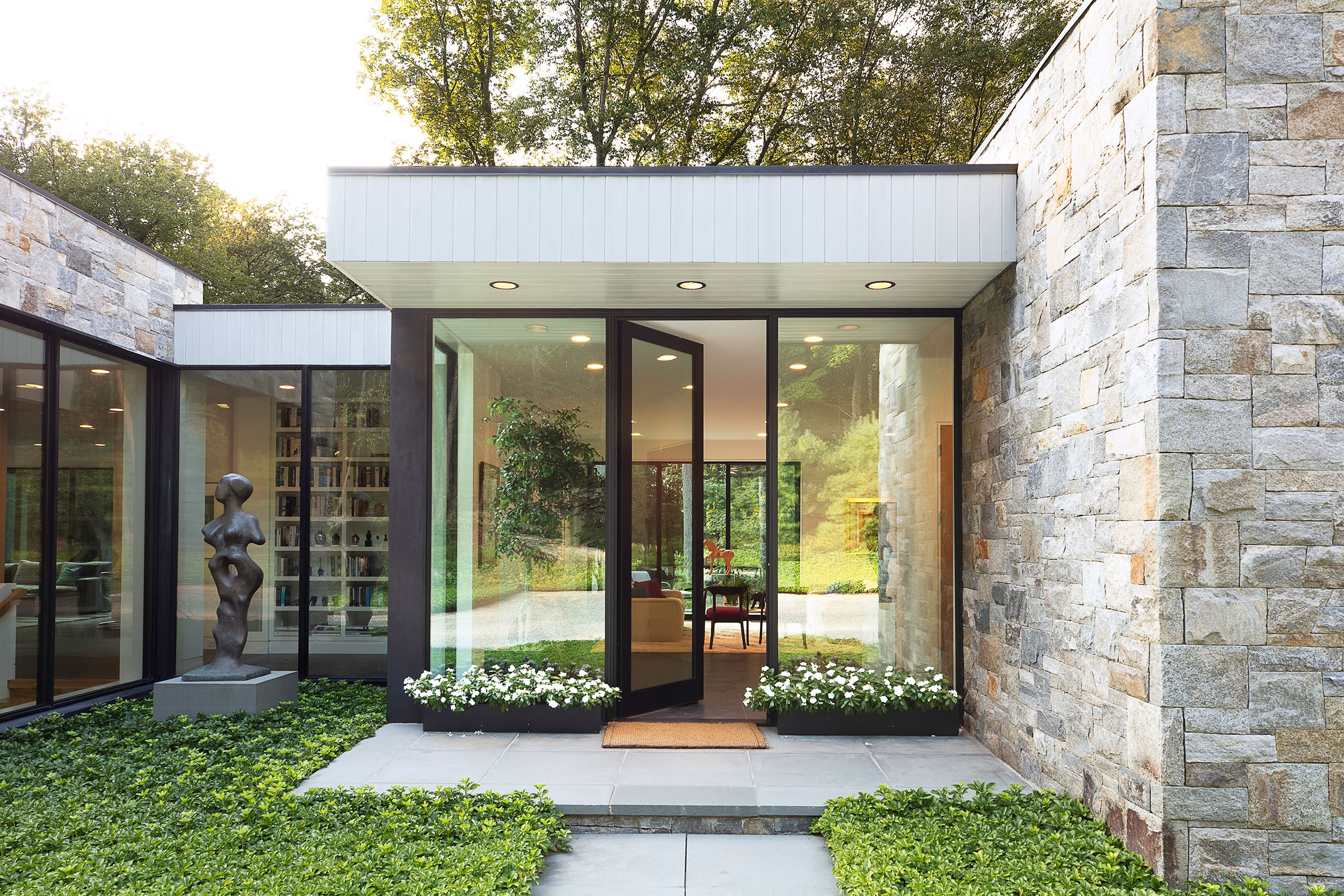 Architect Carol Kurth created a gallery-like feeling that blended her client's art with the trees and stone that surround the property.