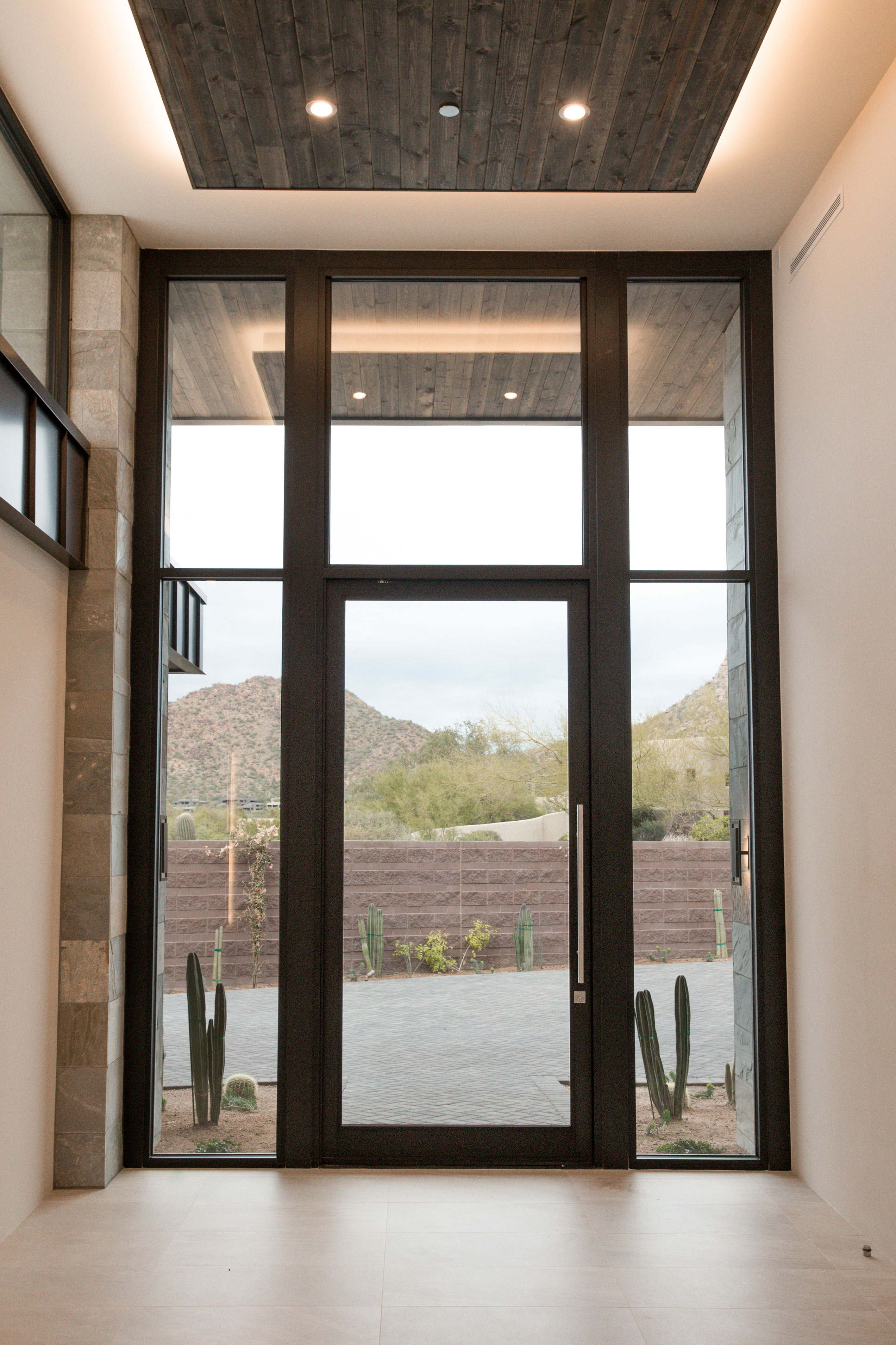 A glass pivot door provides a dramatic entrance into the home.