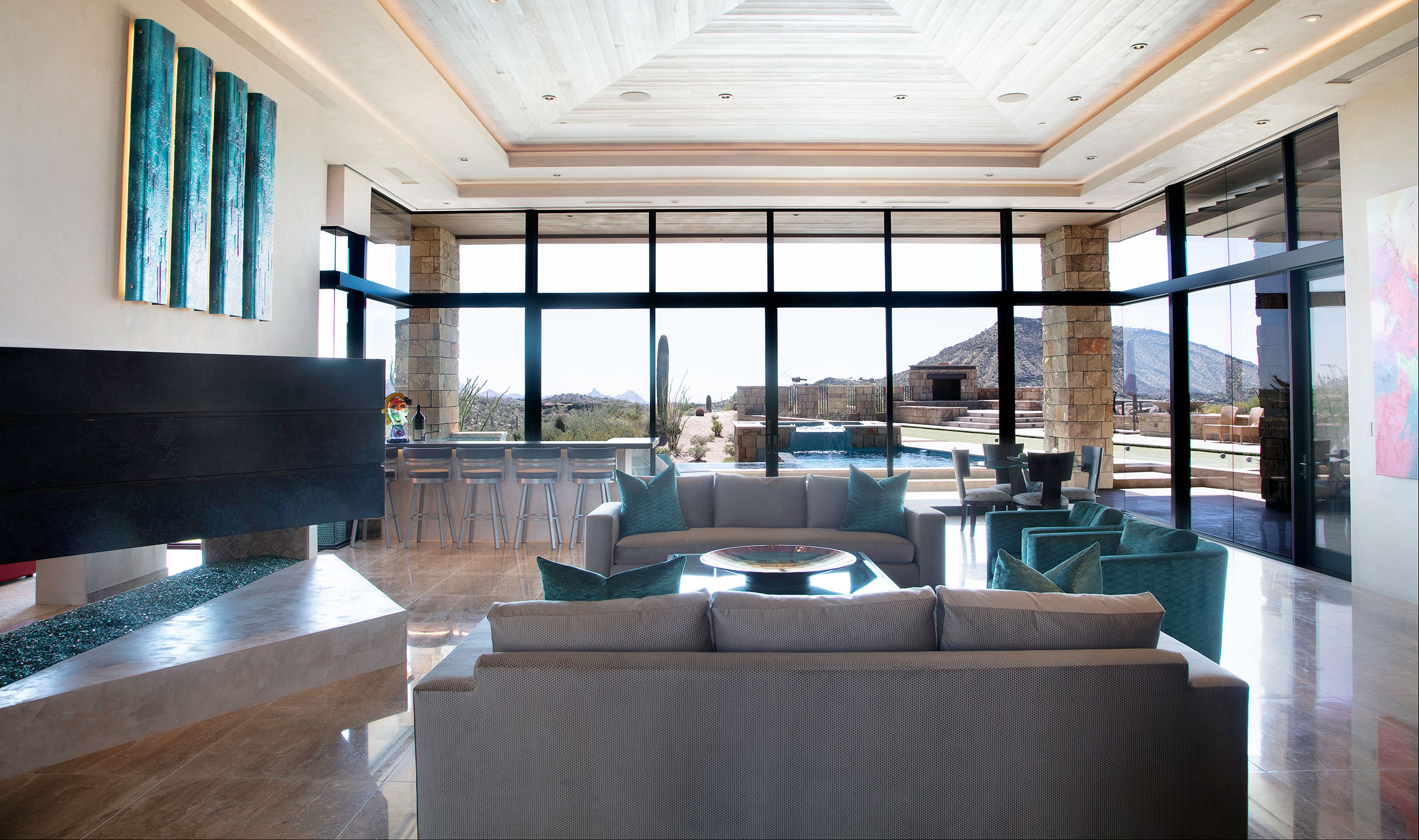 Floor-to-ceiling glass provides panoramic views of the Desert Mountain landscape.