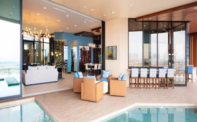 A moving wall of glass opens to merge the interior living lounge with the spacious pool patio.
